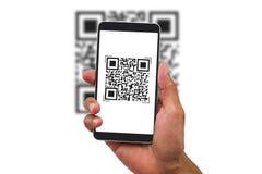 Man& x27; hållande smartphone för s-hand som avläser QR-kod på vit bakgrund royaltyfri bild