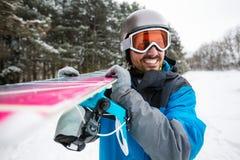 Man hållande snowboard- och hagyckel i vinternatur Arkivbild