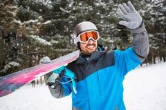 Man hållande snowboard- och hagyckel i vinternatur Arkivfoton