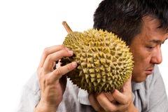 Man hållen och skaka durianfrukt för att bedöma dess mognad Arkivbilder