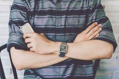 Man hållsmartphonen och korsa en arm för ` som s isoleras på väggbakgrund Royaltyfri Bild