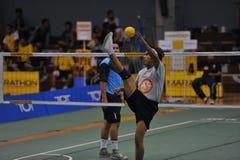 Man höjdpunkten som sparkar bollen till och med det netto i lek av sparkvolleyboll, sepaktakraw Royaltyfri Foto