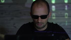 A man hacker man in sunglasses in a dark room works with the program code.  stock footage