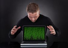 Man or hacker stealing data from a laptop at night. Bending forwards over the keyboard Royalty Free Stock Photo