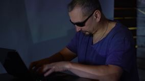 A man hacker in sunglasses in a dark room works with the program code. concept on cybercrime.  stock video