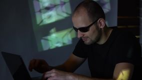 A man hacker in sunglasses in a dark room works with the program code. concept on cybercrime.  stock footage