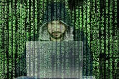 Anonymous person/troll in hooded sweatshirt sits in front of computer.Hacker works with laptop.He has a binary code all around him stock images