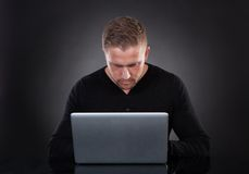 Man or hacker working on a laptop at night Royalty Free Stock Photography