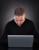 Man or hacker working on a laptop at night Royalty Free Stock Image