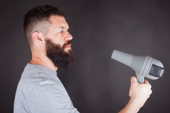 Man with hair dryer. Man wipes his beard with hair dryer Royalty Free Stock Photos