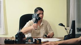 Man in hair net use old 8mm camera in office shooting visitor stock footage
