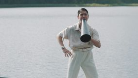 Man in hair net and white clothes standing on boat shouts into megaphone stock video