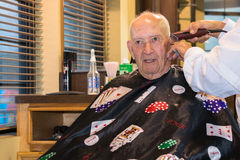 Man Haircut Barbershop. Elderly man wearing a gambling themed barber cape getting a haircut in a barbershop royalty free stock image