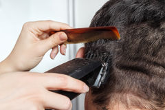 Man haircut by clipper and comb. Brunette man getting a haircut by a professional hairdresser using comb and grooming machine. Closeup man having a haircut with royalty free stock photos