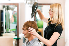 Man at the hairdresser. She has finished the cut and is drying his hair with a blow dryer Stock Photography