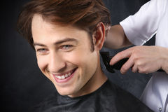 Man at the hairdresser. Portrait of a young white boy while cutting hair in the hair salon Royalty Free Stock Photo