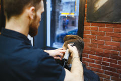 Man at the hairdresser. Portrait of a young white boy while cutting hair in the hair salon Royalty Free Stock Images