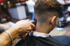 Man at the hairdresser. Portrait of a young white boy while cutting hair in the hair salon Stock Photos
