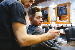 Man at the hairdresser. Portrait of a young white boy while cutting hair in the hair salon Royalty Free Stock Photography