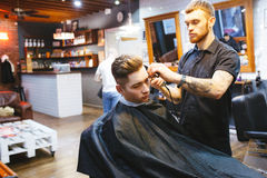 Man at the hairdresser. Portrait of a young white boy while cutting hair in the hair salon Royalty Free Stock Photos