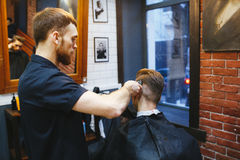 Man at the hairdresser. Portrait of a young white boy while cutting hair in the hair salon Stock Image