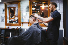 Man at the hairdresser. Portrait of a young white boy while cutting hair in the hair salon Stock Photo