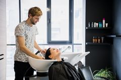 Man hairdresser washing head client. A man hair master watering a girl`s hair with a shower in a hair studio. Man hairdresser washing head client. A men hair royalty free stock photo