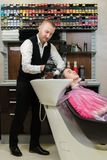 Man hairdresser washing head client the shampoo off a client`s head royalty free stock photography