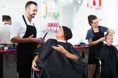 Man hairdresser and woman client Stock Images