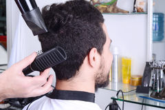 Man in hairdressing and drying his hair with a hairdryer. Close up of young man in hairdressing and drying his hair with a hairdryer Royalty Free Stock Photos