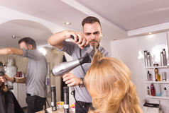 Man hairstylist blow drying comb roller Royalty Free Stock Image