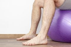 Man with hairy legs sitting on a fitness ball stock photo