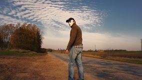 Man in Halloween mask with a knife in his hands walking along the road`s edge stock video