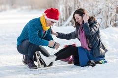 Man halping to wear ice skates to his girlfriend. Stock Photos