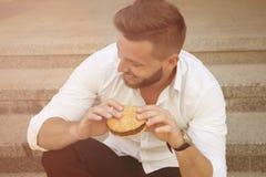 Man with hamburger Stock Images