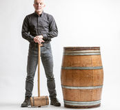 Man with hammer and barrel. Man in grey jeans and shirt standing leaning on big wooden hammer handle, near old wooden barrel against white background stock image