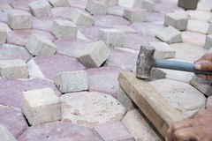 Man is hammer brick block for pathway Stock Image