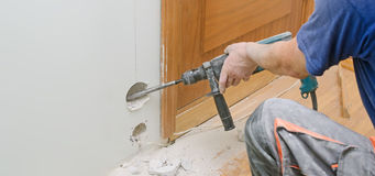 Man with Hammer drill doing hole for socket. Royalty Free Stock Photography