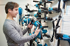 Man with hammer drill in hardware store Stock Photo