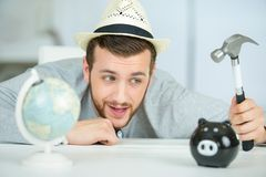 Man with hammer going to break piggy bank Stock Photography