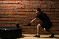 Man with a hammer in his hand beats on a tire, training crossfit against a brick wall. Man with a hammer in his hand beats on a tire, training crossfit against Stock Image