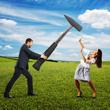 Man with hammer and scared woman Stock Photo