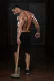 Man With Hammer Showing His Well Trained Body. Portrait Of A Physically Fit Man Showing His Well Trained Body And Holding A Hammer Royalty Free Stock Photo