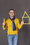Man with hammer showing house frame concept. Happy man showing a hammer in one hand, and a house home concept - frame of yellow meter in another hand Stock Photography