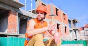 Man hammer take break working day at construction site. Builder vest and helmet construction site sit relaxing. Guy royalty free stock images