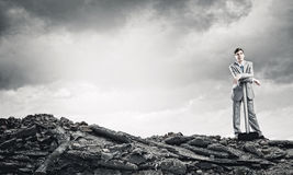 Man with hammer. Young businessman with hammer standing on ruins Royalty Free Stock Photos