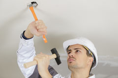 Man hammering ceiling Royalty Free Stock Photo