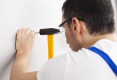 Man hammering nail into wall Royalty Free Stock Photography