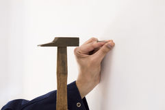 Man hammering a nail into a wall white Stock Image