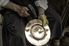 Man hammering tinplate Royalty Free Stock Images